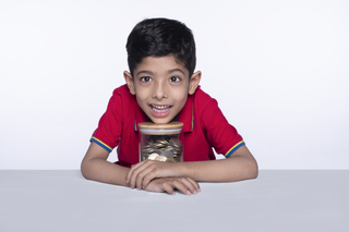 Happy male junior child with a clear jar full of coins (money), white background - savings concept