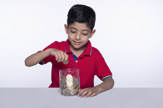 Cheerful child boy putting coins in a glass jar. Concept of saving. Child saving money