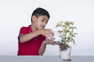Closeup of an Indian child boy putting coins in a plant pot, white background, isolated, studio, Investment concept