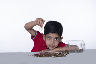 Portrait of a cute charming boy with a coin in his hand - looking at camera against the white background