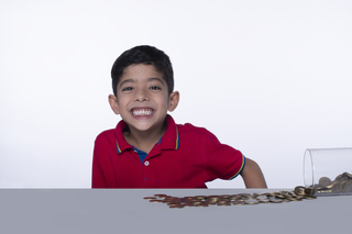 Cheerful Indian child with coins and glass jar, posing towards the camera against a white background
