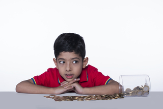 Adorable cute child thinking while counting coins in a glass jar, white background - money saving concept