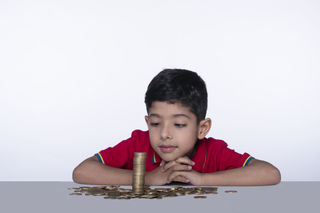 Happy child boy making stacks of coins on the table - Children and money concept