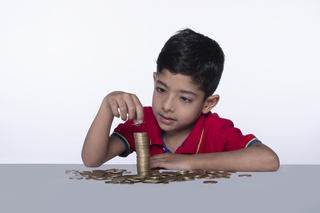 Happy little kid stacking coins on the table - Childhood and money counting concept.
