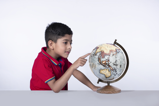 Closeup portrait of an intelligent child boy pointing on globe leaning against the desk - white background