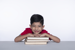 Smiling Indian boy with books for an education portrait - isolated over a white background