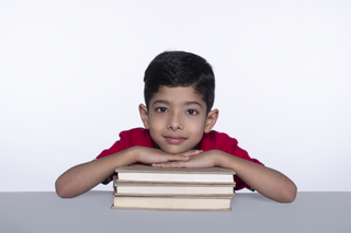 Smiling little preschooler - a stack of books on the table, white background, isolated, studio