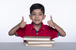 Portrait of a cute little boy pointing thumbs up while studying. White background