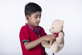Cute Indian preschool child kid pretending to be a nurse treating a fluffy patient at home - medical and childhood concept