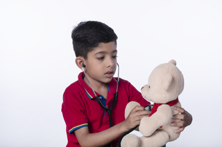 Little child boy playing doctor game with a stethoscope and examining a teddy bear - childhood and healthcare concept