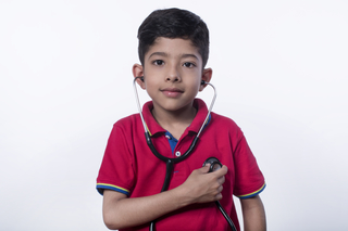 Closeup of cute little child boy playing with a stethoscope against the white background