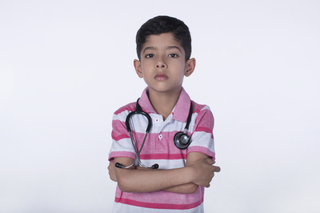 A serious male junior doctor posing towards the camera with a stethoscope - childhood