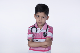 Portrait of a junior doctor with stethoscopem\,  crossed arms posing towards the camera, white background