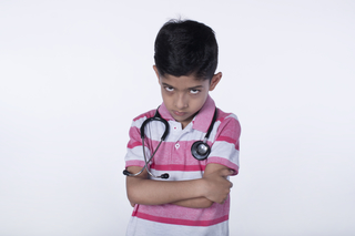 Angry young Indian boy playing and posing with a stethoscope, white background - healthcare