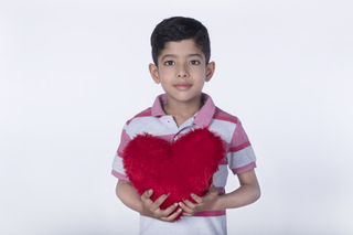 Closeup of an attractive little boy holding a red soft heart with both hands. White background, isolated, childhood