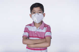 Portrait of cute little Indian boy wearing face, looking up, pollution, health, isolated over white background