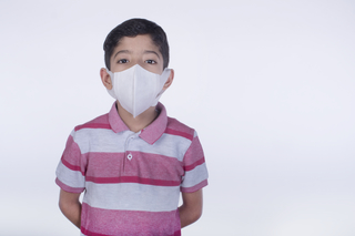 Portrait of an Indian little boy standing with a mask on face, anti pollution mask, health, white background