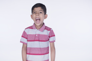 Closeup portrait of a naughty boy screaming loudly against the white background