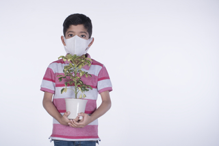 Attractive child boy holding a plant, wearing a protective anti-pollution mask, white background - save nature, environment
