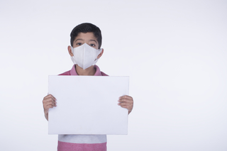 Portrait of a little child boy wearing a protection mask and holding a banner - pollution, health