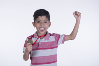 Happy child boy holding a gold medal and raising another hand against the white background