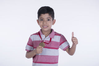 Happy child boy with a gold medal, thumbs up against white background- winning concept