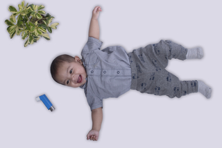 Happy cute little infant laying down and playing. Healthy environment and fresh air concept, white background