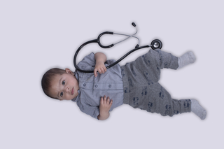Surprised baby infant laying down with stethoscope against the white background, studio, isolated