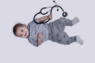 Sweet little infant playing with medical instrument (stethoscope) on white background - studio isolated