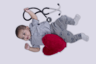 Adorable smiling baby boy lying with red heart-shaped soft toy and stethoscope - childhood, newborn baby, health