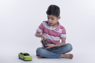Cute little boy playing with a remote controlled toy car against the white background - childhood