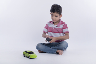 Smart boy holding a remote and playing with a toy car - White background