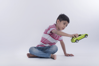 Little boy sitting and playing with a green toy car - Childhood, young years