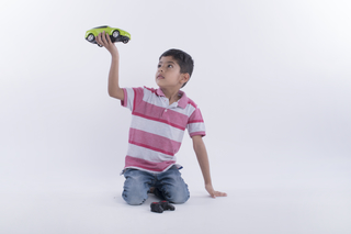 Portrait of a boy playing with remote control car - studio shot isolated on white background