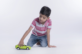 Little child playing with toy car at home with white background
