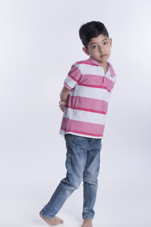 Innocent boy standing with a mischevious look - white background studio isolated