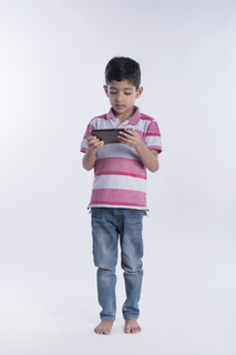 Young 5 year old boy watching a movie in his smart phone - standing in front of white background
