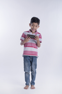 Portrait of an Indian boy watching a video on the mobile studio - isolated on white background. Technology addiction