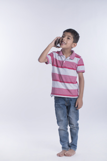 Cheerful boy standing and talking on mobile phone with white background