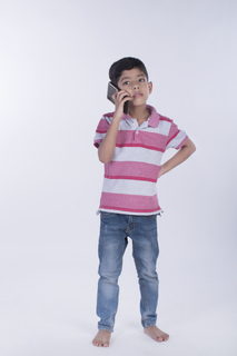 Male junior talking on a mobile phone on white background - Young generation