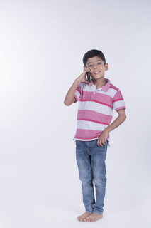 Full-length image of a proud boy talking on a mobile phone - isolated image in the studio