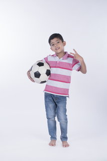 Cute boy holding a ball and making a victory gesture with two fingers - isolated on a studio white background