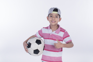Portrait of a boy holding a soccer ball on white background - Sport concept