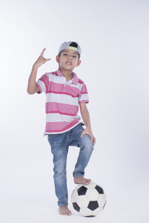 Male junior standing with a football on a white background - full-length image