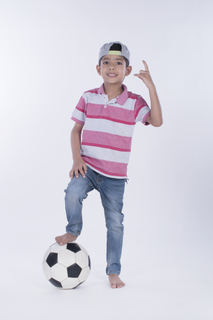 Attractive boy with a soccer ball in studio -isolated white background image. Sports concept
