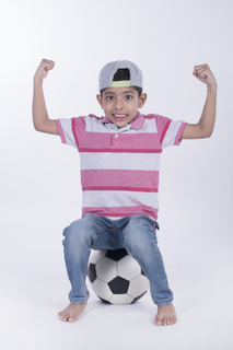 Portrait of a happy child playing with a ball, full-length image with white background