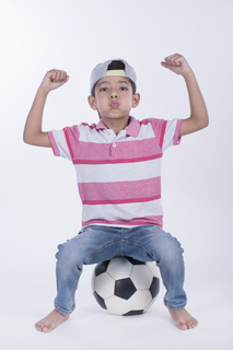 Cheerful young Indian boy sitting on a soccer ball - full length image with white background