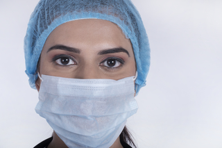 Close up portrait of a female doctor or nurse wearing a protective mask and cap. White background