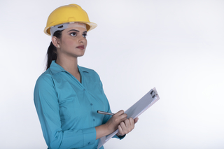 Young female architect at the construction site with clipboard looking upward. White background - workaholic concept