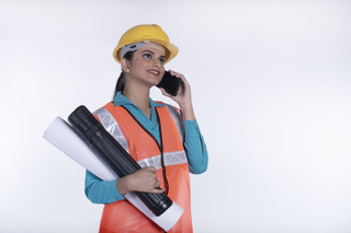 Young smiling businesswoman (builder, engineer, architect) talking on mobile phone and holding blueprints